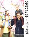 肩車をする笑顔の30代夫婦と2人の子供の家族と春の満開の桜の背景 49712360