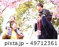 肩車をする笑顔の30代夫婦と2人の子供の家族と春の満開の桜の背景 49712361