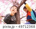 木登りする2人の子供兄弟と春の満開の桜の背景 49712368