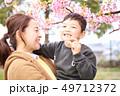 抱っこする30代母親と子供の家族と春の満開の桜の背景 49712372