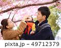 抱っこする30代母親と子供の家族と春の満開の桜の背景 49712379