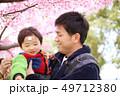 30代父親と子供の家族と春の満開の桜の背景 49712380