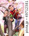 笑顔の30代母親と2人の子供の家族と春の満開の桜の背景 49712381