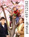 笑顔の30代夫婦と2人の子供の家族と春の満開の桜の背景 49712382