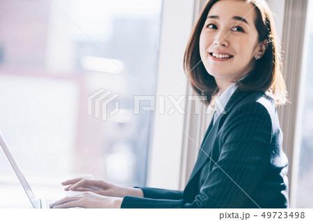 窓際の席でパソコンに向かう上司の女性 49723498