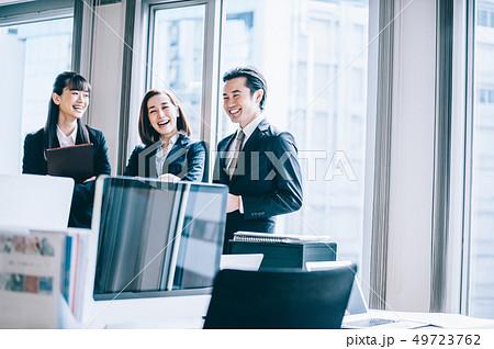 窓際に立ち談笑する上司と部下たち 49723762