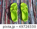 Pair plastic green sandals on handmade carpet background 49726330
