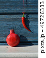 Red chili pepper hanging on wooden wall and pomegranate on shelf 49726333