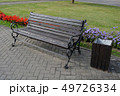 Modern wooden bench with metal frame in city street and flowerbeds 49726334