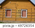 begin instaling wooden planks on old house for insulation 49726354