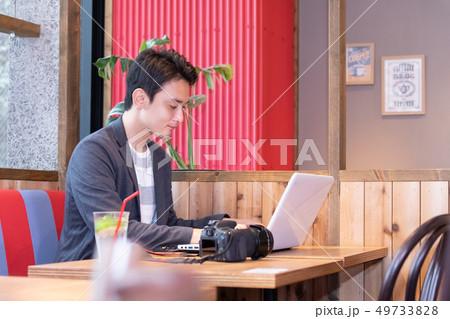 カフェでリラックスする男性 一眼レフカメラ 49733828