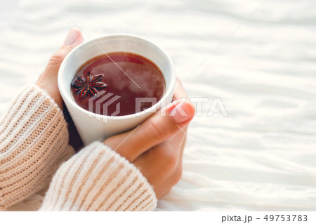 Women holds a cup of hot tea with anise star. Cozy 49753783