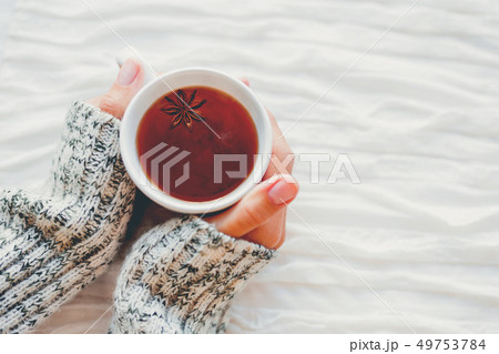 Women holds a cup of hot tea with anise star. Cozy 49753784