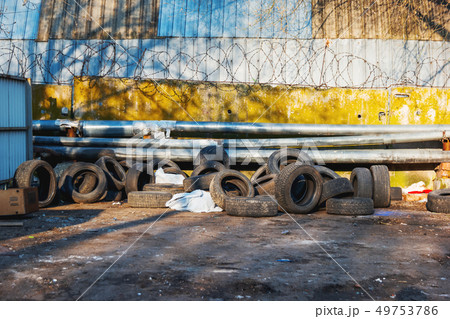 Old car tires are piled up against a fence 49753786