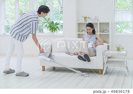 掃除機をかける男性とソファに座って両足を上げる女性 49836178