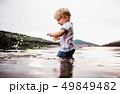A wet, small toddler boy standing outdoors in a river in summer, playing. 49849482