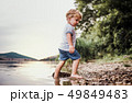 A wet, small toddler boy standing outdoors in a river in summer, playing. 49849483