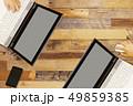 木目のテーブルとノートパソコンを使う2人の手 49859385