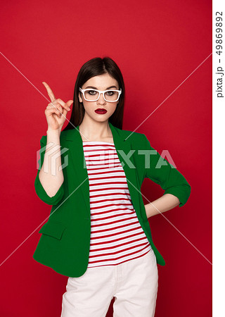 Confident stylish brunette lady isolated on red 49869892