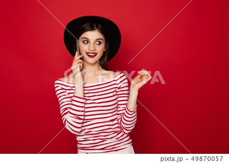 Coquettish young girl talking by mobile phone 49870057