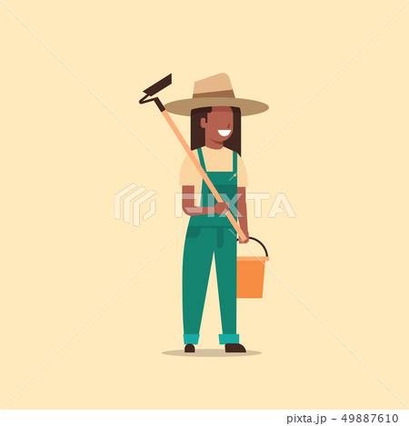 female gardener holding hoe and bucket african american country woman working in garden gardening 49887610