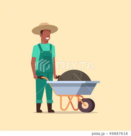 gardener man pushing wheelbarrow full of earth compost african american male farmer working in 49887618