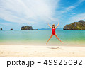 Young attractive woman jumping on the sea beach 49925092