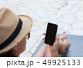 Young woman using smartphone near a swimming pool 49925133