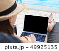Young woman using laptop near a swimming pool 49925135