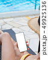 Young woman using smartphone near a swimming pool 49925136