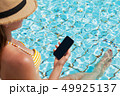 Young woman using smartphone near a swimming pool 49925137