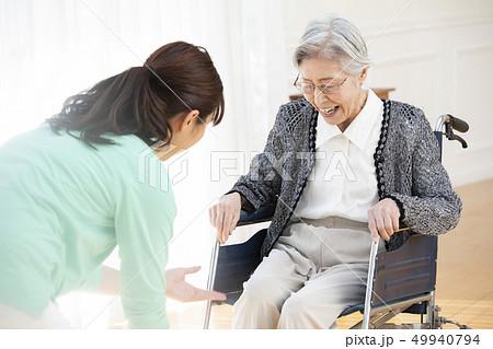 車椅子の高齢者とヘルパー 49940794
