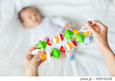 Woman holding baby's first toy - colorful rattle 49970506