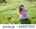 beautiful blonde woman collects spring color in the garden 49997993