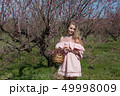beautiful blonde woman in a flowered Peach Garden in spring with pink flowers 49998009