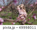 beautiful blonde woman in a flowered Peach Garden in spring with pink flowers 49998011