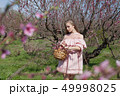 beautiful blonde woman in a flowered Peach Garden in spring with pink flowers 49998025