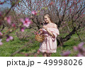 beautiful blonde woman in a flowered Peach Garden in spring with pink flowers 49998026
