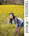 奈良県橿原市の藤原宮跡の菜の花畑を背景にしているショートパンツ姿の笑顔の若い女性 50020681
