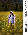 奈良県橿原市の藤原宮跡の菜の花畑を背景にしているフードをかぶっているショートパンツ姿の若い女性 50020683