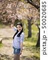 奈良県橿原市の藤原宮跡の葉桜の下にいる笑顔の若い女性 50020685
