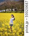 奈良県橿原市の藤原宮跡の菜の花畑を背景にしているショートパンツ姿の笑顔の若い女性 50020687