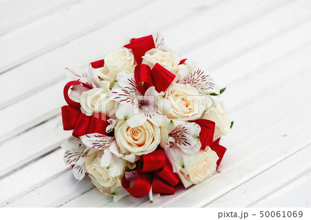 Bridal bouquet with red ribbons, beige roses and 50061069