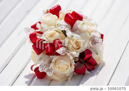 Bridal bouquet with red ribbons, beige roses and 50061070