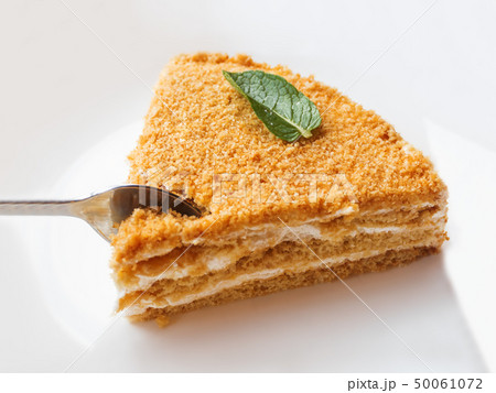 White plate with honey cake. Tasty dessert with 50061072