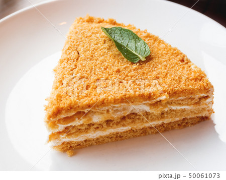White plate with honey cake. Tasty dessert with 50061073