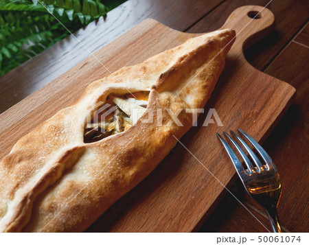 Baked bun in the shape of a boat with mozzarella 50061074