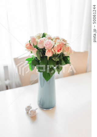 Bouquet of peach colored roses in light blue vase 50061244