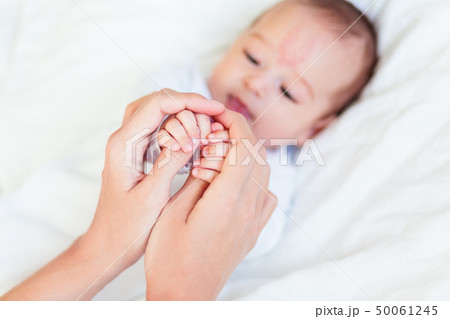 Mother holds newborn baby's hands. Tiny fingers 50061245