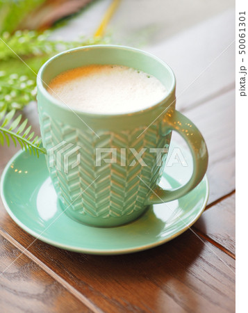Porcelain aquamarine colored cup with cappuccino. 50061301